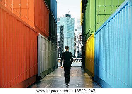 Businessperson walking towards city on concrete path between cargo containers. Success concept 3D Rendering
