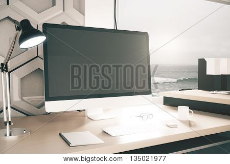 Closeup of creative designer desktop with blank computer monitor lit lamp coffee cup patterned honeycomb wall in the background and window with seaside view. Mock up 3D Rendering