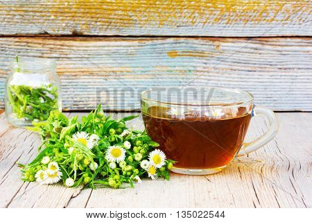 glass cup of tea with camomile flowers and camomile on an old wooden table in the cracks close up