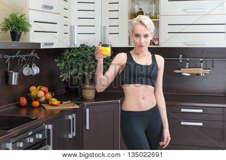 sporting woman holding orange juice in modern kitchen