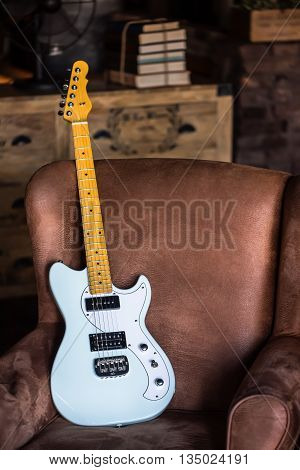 Electric Guitar Leaning Against a Couch with Grunge Background. Electric Guitar Light Blue Finish. Still life with Electric Guitar.
