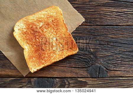 Slice of toasted bread on wooden table top view. Space for text