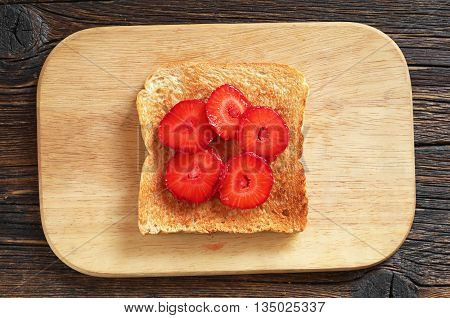 Toast with fresh strawberries on wooden table top view