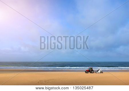 Tractor cleaning an empty beach in the early morning of a summer day