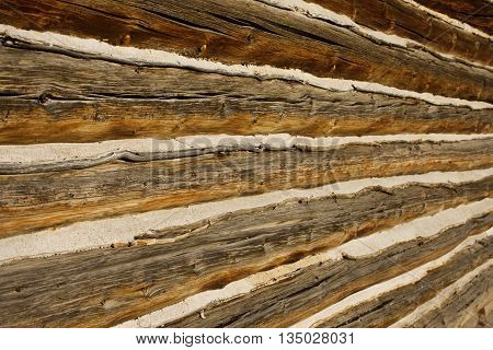 rustic wooden log cabin siding with golden brown tones