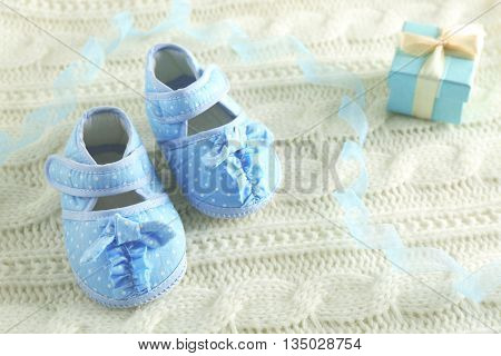 Baby booties on knitted plaid, closeup