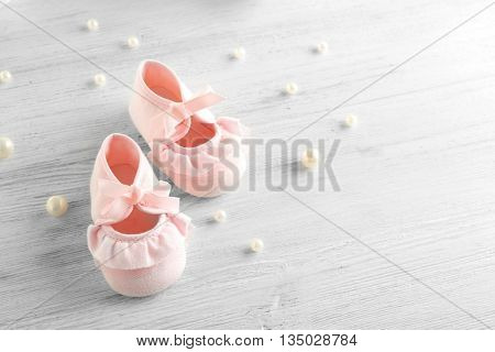 Baby booties on wooden table, closeup