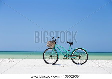 Turquoise bike parked at the beach, in the Mexican Caribbean