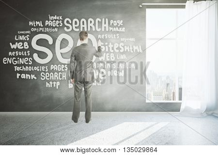 Search engine optimization concept with businessman writing on chalkboard wall in room with concrete floor window with curtain and city view. 3D Rendering