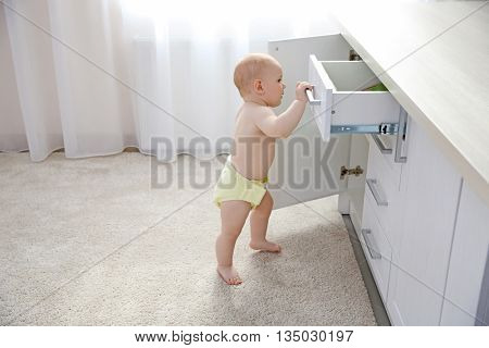 Baby boy playing with locker in the room