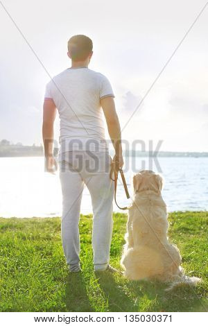 Man with dog on the riverside