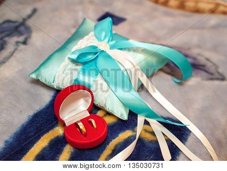 Gold wedding rings in a red box near the pincushion