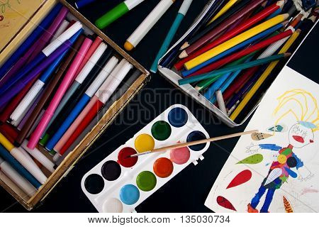 Children's paints, pencils, markers and drawing on the black table, the view from the top