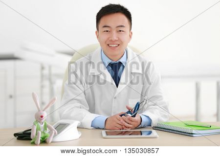 Handsome pediatrician doctor in office