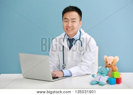 Handsome pediatrician doctor with laptop and teddy bear in office