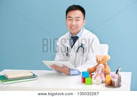 Handsome pediatrician doctor with tablet in office