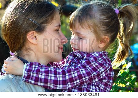 Mother and daughter looking at each other in a sunny day