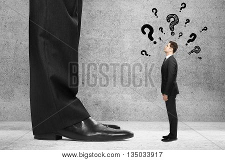 Businessman miniature with questions standing next to boss's feet and looking up at him on concrete background. Mentoring concept