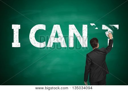 I can self motivation concept. Businessman wiping letter 'T off chalkboard so that it reads i can