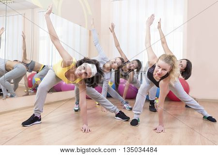 Group of Five Professional Sportswomen Making Stretching Exercises with Trunk Bending in Sport Class. Horizontal Image Orientation
