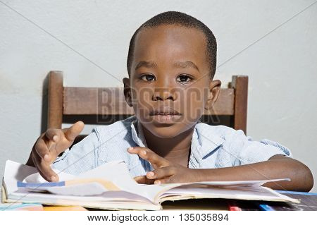 This child sitting on a chair , his reading book in front of him, looking in the camera objective.