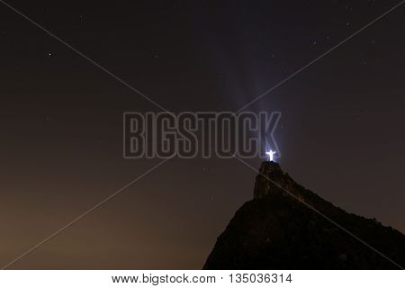 Rio de Janeiro, Brazil - June 16, 2016: Illuminated Christ the Redeemer statue reflecting light into the sky at night.