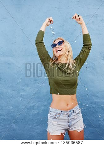 Portrait of beautiful young woman throwing glitters on herself while standing against blue wall