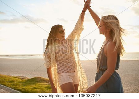 Two Young Women Giving High Five On The Beach