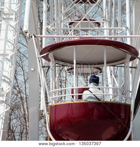 Sad girl on a Ferris wheel at amusement park winter cold depression. Woman on observation wheel cabin ride close-up at fair