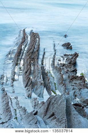Twilight Ocean Coast With Ribbed Stratiform Rock.