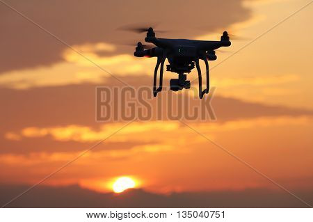 KAGAWA, JAPAN - JUNE 19, 2016: Remote controlled drone Dji Phantom 3 equipped with high resolution video camera hovering in air and sunset.