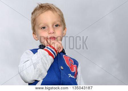 Portrait of a little blond boy on a light gray background cloudy sky