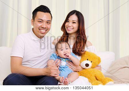Indooor portrait of beautiful asian family sitting on sofa