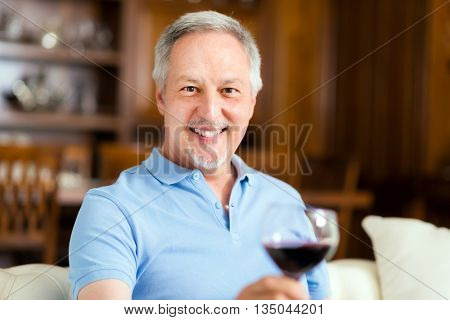 Senior man enjoying a glass of red wine