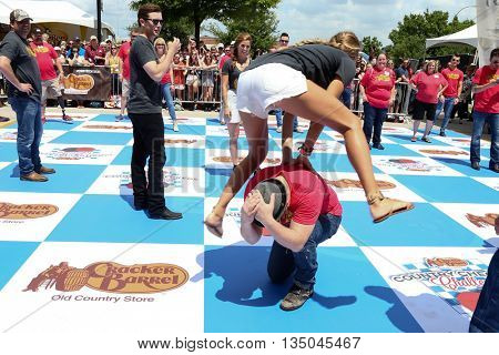 ARLINGTON, TX - APR 18: Lauren Akins jumps over Kristian Bush at the Cracker Barrel Old Country Store Country Checkers Challenge at Globe Life Park in Arlington on April 18, 2015 in Arlington, Texas.