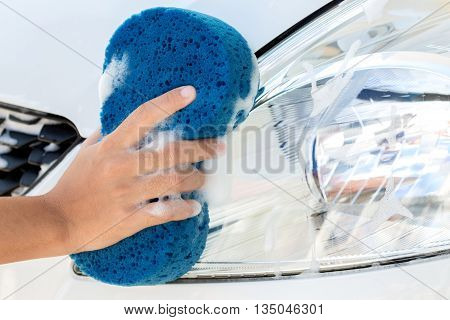 close up hand using sponge washing car