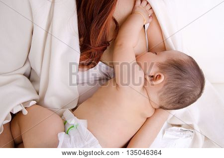 Six months old baby boy drinking breastmilk