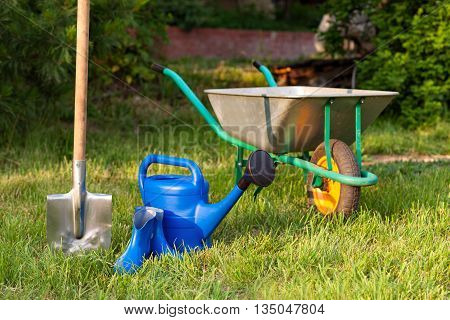 Blue watering can and rubber boots on a background of green lawn. Bright inventory gardener. Trolley and shovel for the garden care.