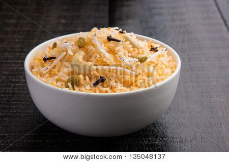 coconut rice, coconut sweet rice, sweet coconut rice also known as narali bhat in marathi, favourite Indian sweet, konkan food, kerala food, saffron, cashew, cloves, served in white bowl, isolated