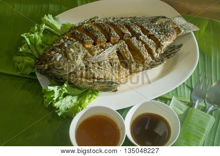 fish grilled on a white disc with sause on banana leaf