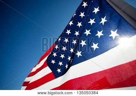 United States flag blows in the wind against a blue sky on a sunny day