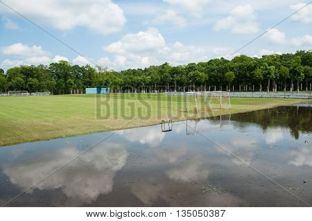green football field flooded with rain water