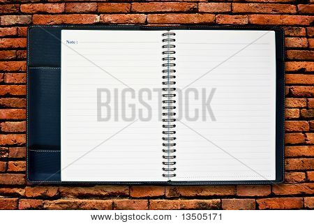 Blank Notebook On Brick Wall