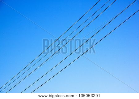Electric Cables Stretching Across Blue Sky