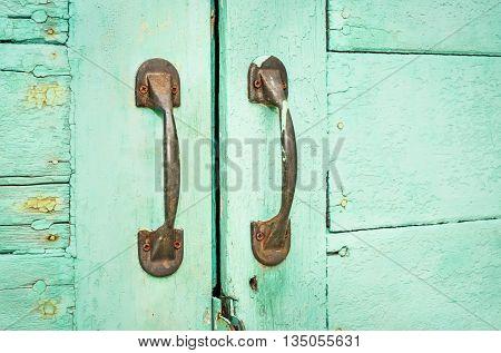 Rusty door handles on blue wooden door