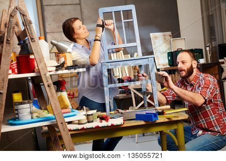 Busy couple renewing chair in home workshop.