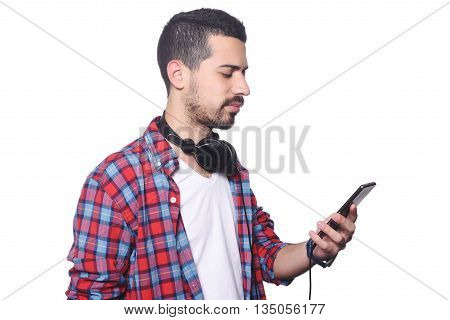 Portrait of a young latin man typing on his smartphone and using black headphones. Isolated white background.