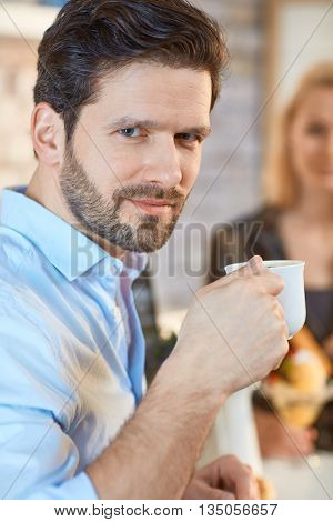 Closeup portrait of young man holding coffee cup, drinking, looking at camera with small smile.