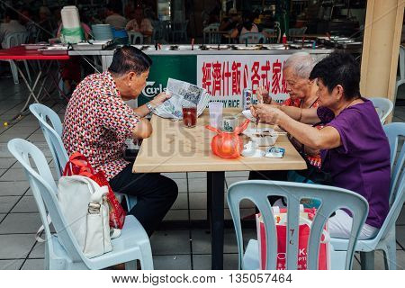 KUALA LUMPUR MALAYSIA - MARCH 17: Group of senior Chinese people having a breakfast in traditional Kopitiam Chinatown Kuala Lumpur Malaysia on March 17 2016.