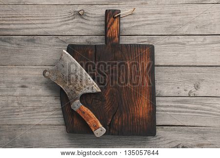 Chopping board block on wooden background and cleaver